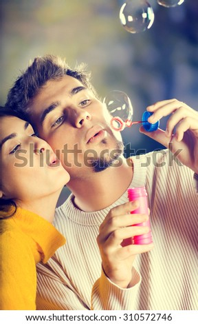 Young attractive happy couple blowing bubbles outdoors - stock photo