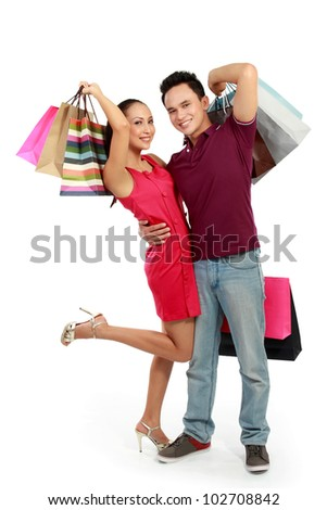 young attractive happy couple having fun with shopping bags - stock photo