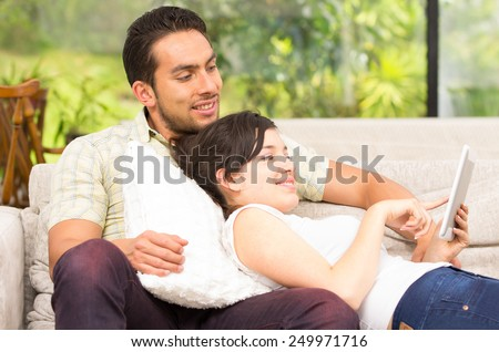 young attractive happy couple relaxing in the sofa using tablet - stock photo