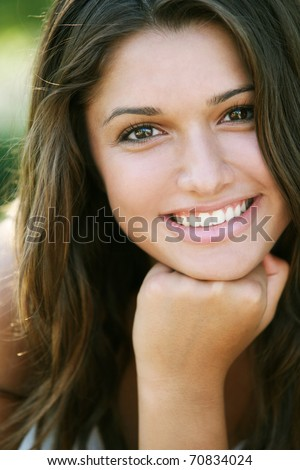 Young attractive happy girl with long hair posing outdoor. - stock photo