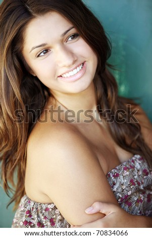 Young attractive happy girl with long hair posing outdoor.