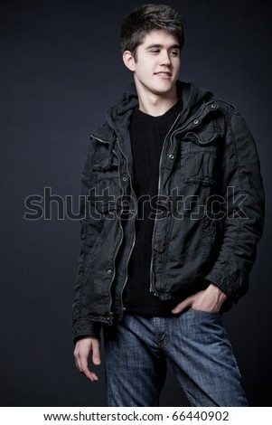 Young attractive happy man wearing black jacket with hood. - stock photo