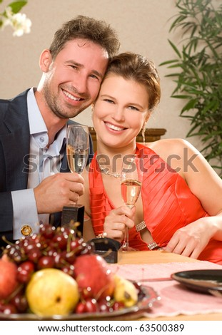 Young attractive happy smiling couple celebrating with champagne, indoors