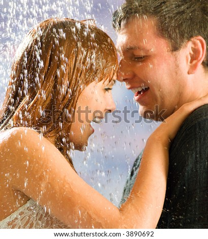 Young attractive happy smiling couple hugging on the street, under a rain, in passion