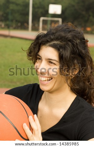 Young, attractive, happy woman is standing on an outdoor basketball court.  She is holding a basketball and smiling and laughing.  Vertically framed shot. - stock photo