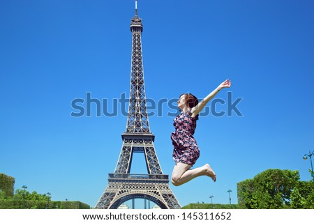 Young attractive happy woman jumping for joy against Eiffel Tower in Paris, France - stock photo