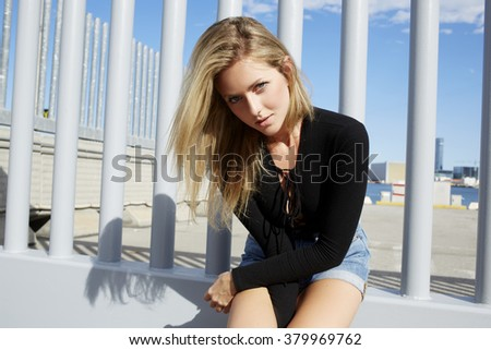 Young attractive hipster girl posing while sitting outdoors in sunny summer day during her recreation time, charming woman looking at camera while relaxing after walking outside during weekend - stock photo