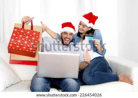 young attractive Hispanic couple with santa hat together in love on sofa couch at home with computer laptop holding shopping bags purchasing online Christmas presents with credit card on internet