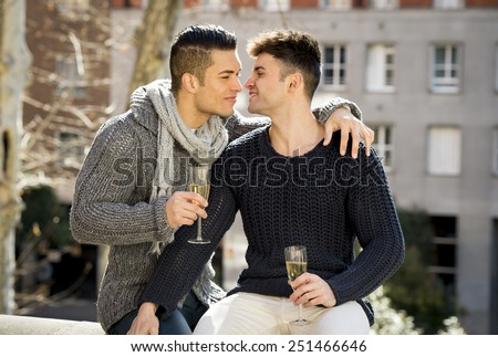young attractive Hispanic gay men couple kissing celebrating together Valentines day or anniversary champagne toast on street smiling happy in love on urban background  - stock photo