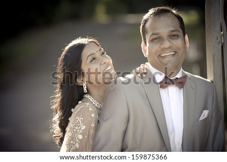 Young attractive indian couple laughing together outdoors - stock photo