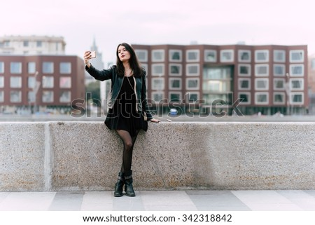 Young attractive lady dressed in trendy clothes making self portrait with smart phone camera, charming female posing while photographing herself for social network picture during walking outdoors  - stock photo