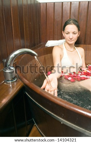 Young attractive lady, relaxing in a bathtub, playing with the running faucet. Multicolored rose petals float on the surface of the bathtub. Vertically framed shot. - stock photo