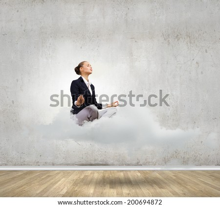 Young attractive lady sitting on cloud and practicing yoga - stock photo