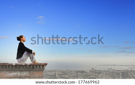 Young attractive lady sitting on top of building - stock photo