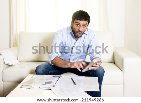 young attractive latin american business man at home sitting on sofa with credit card and calculator accounting costs, charges, taxes and mortgage for paying bills looking worried and stressed  - stock photo