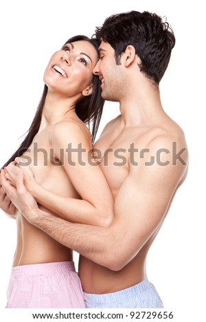 Young attractive laughing couple with the man standing behind the woman cupping her bare breasts in his hands, three quarter studio portrait on white - stock photo