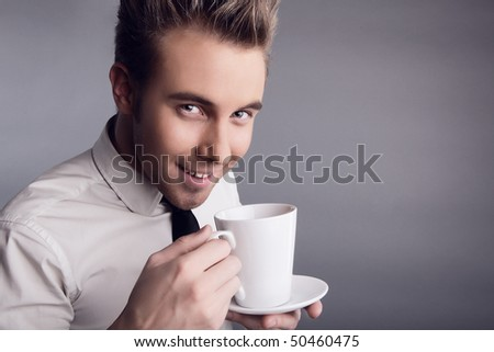 Young attractive macho drinking coffe - stock photo