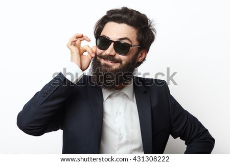 Young attractive macho stylish fashionable guy. Happy man in a black suit and sunglasses with a beard touching his mustache curls on white background.
