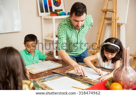 Young attractive male art teacher helping one of his students with her drawing during class - stock photo