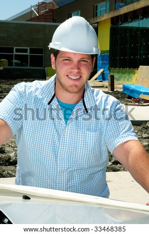 Young Attractive Male Construction Site Foreman, Checking The Blueprints - stock photo