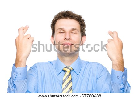 young attractive male holds his fingers crossed and eyes closed, wishful thinking, studio shoot isolated on white background - stock photo