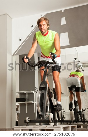 Young attractive male is working out in a cycling gym. - stock photo