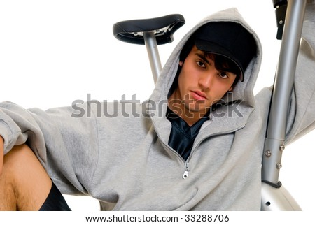 Young attractive male teenager in front of fitness bike, bicycle. Studio shot, white background.