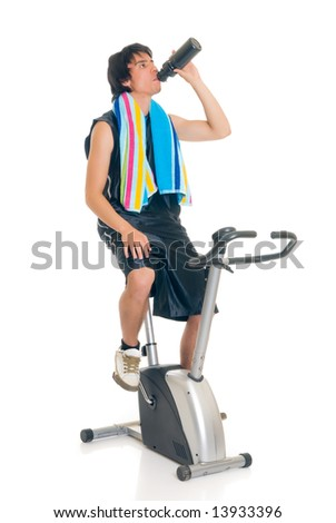 Young attractive male teenager on fitness bike, bicycle. Studio shot, white background. - stock photo