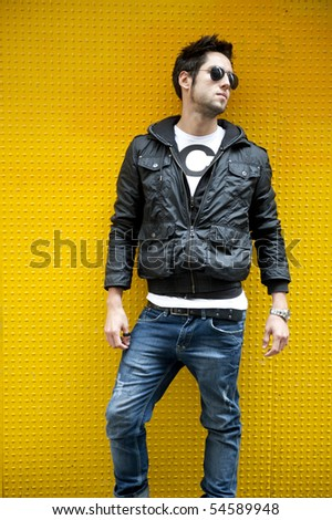Young attractive man against yellow wall - stock photo