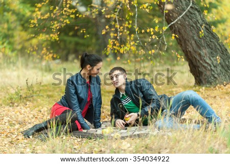Young attractive man and girl sit on plaid. Autumn picnic rest on nature