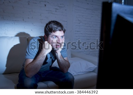 young attractive man at home lying on couch at living room watching tv holding remote control looking mesmerized and intense in television addict concept - stock photo