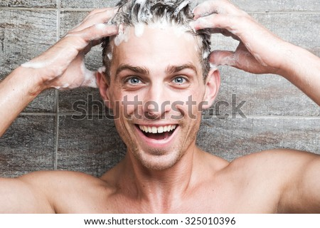 Young attractive man cheerfully washes her head - stock photo