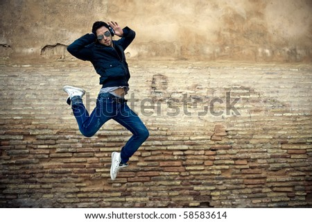 Young attractive man dancing in urban background - stock photo