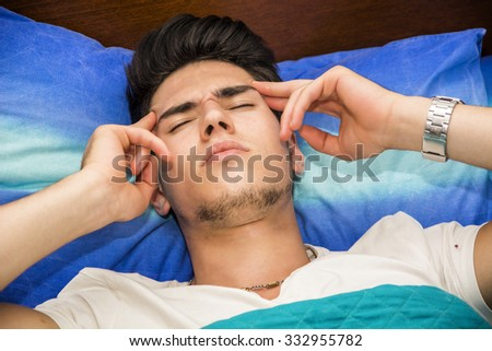 Young Attractive Man Holding Head and Lying in Bed - Close Up of Sick Man with Headache Recuperating in Bed - stock photo