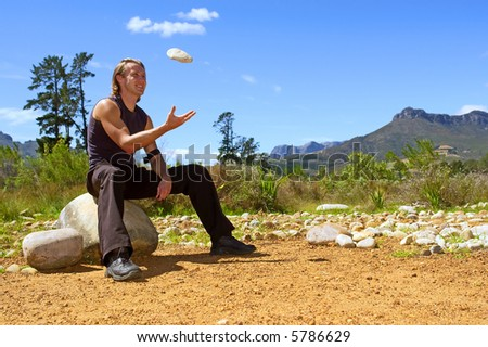 Young attractive man is tossing a rock - and misty majestic mountains as a background. Shot in Jan Marais nature reserve, Stellenbosch, Western Cape, South Africa.