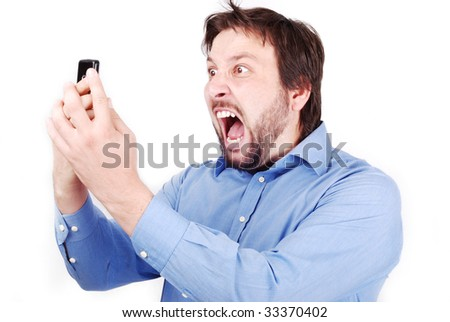 Young attractive man is yelling on his cell phone - stock photo