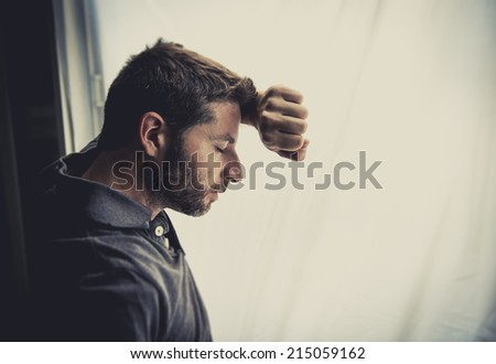 young attractive man leaning desperate on window glass at home, looking worried, depressed, thoughtful and lonely suffering depression in work or personal problems concept with copy space - stock photo