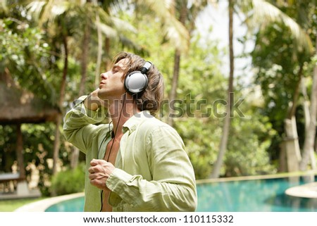 Young attractive man listening to music with headphones while dancing near a swimming pool in a tropical garden. - stock photo