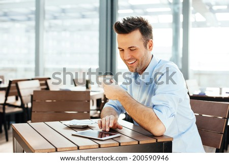 Young attractive man looking at a tablet and enjoying a cup of coffee - stock photo