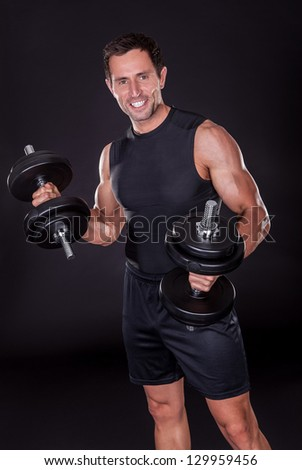 Young Attractive Man Pumping Weights In A Black Tank Top - stock photo