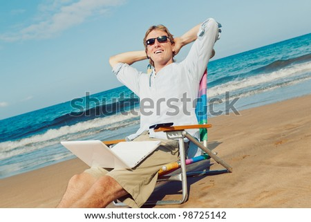 Young Attractive Man Relaxing at the Beach with Laptop Computer - stock photo