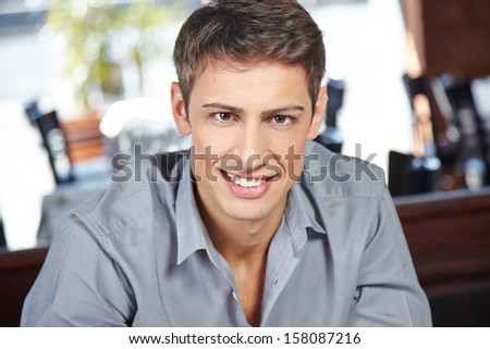 Young attractive man sitting in a restaurant and smiling into the camera