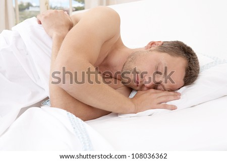 Young attractive man sleeping in bed. - stock photo