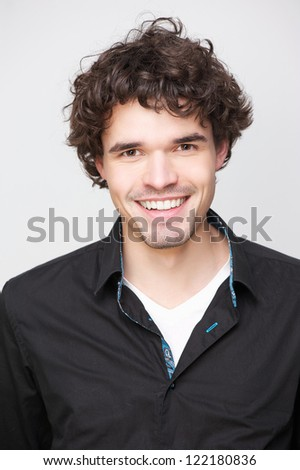 Young attractive man smiling and looking at camera. he is wearing a black shirt and has a friendly expression on his face - stock photo