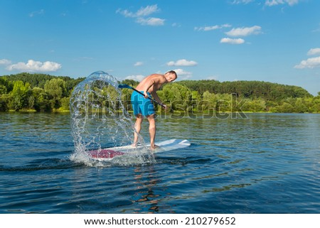 Young attractive man splashing water on stand up paddle board in the lake, SUP - stock photo