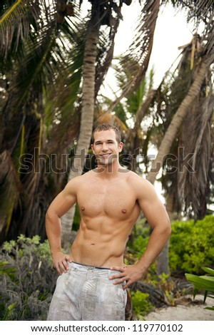 Young attractive man standing shirtless in a confident pose. - stock photo