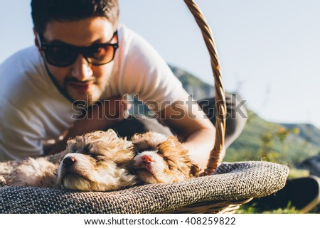 Young attractive man taking care of his sleepy puppies - stock photo