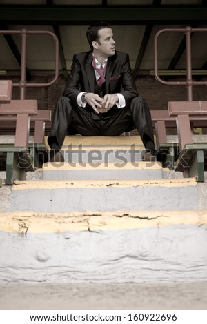 Young attractive man wearing a dress suit sitting on grand stand stairs