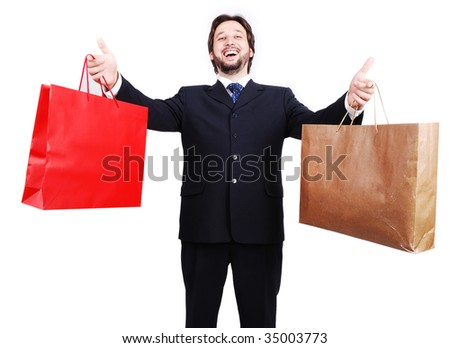 Young attractive man wearing suit and holding shopping bags - stock photo