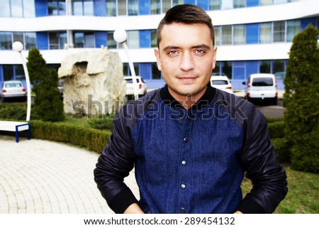 Young attractive men in stylish jeans coat,with modern haircut  posing at  modern white blue background - stock photo